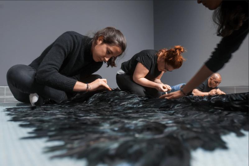 En la imagen varios estudiantes tejen un manto de plumas negras, que forman parte de una pieza de la artista Cecilia Paredes.
