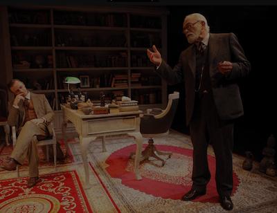 """Un actor apático mira a otro declamando en una escena de """"La sesión final de Freud"""" representada en el MUN por Unir Teatro en 2016"""