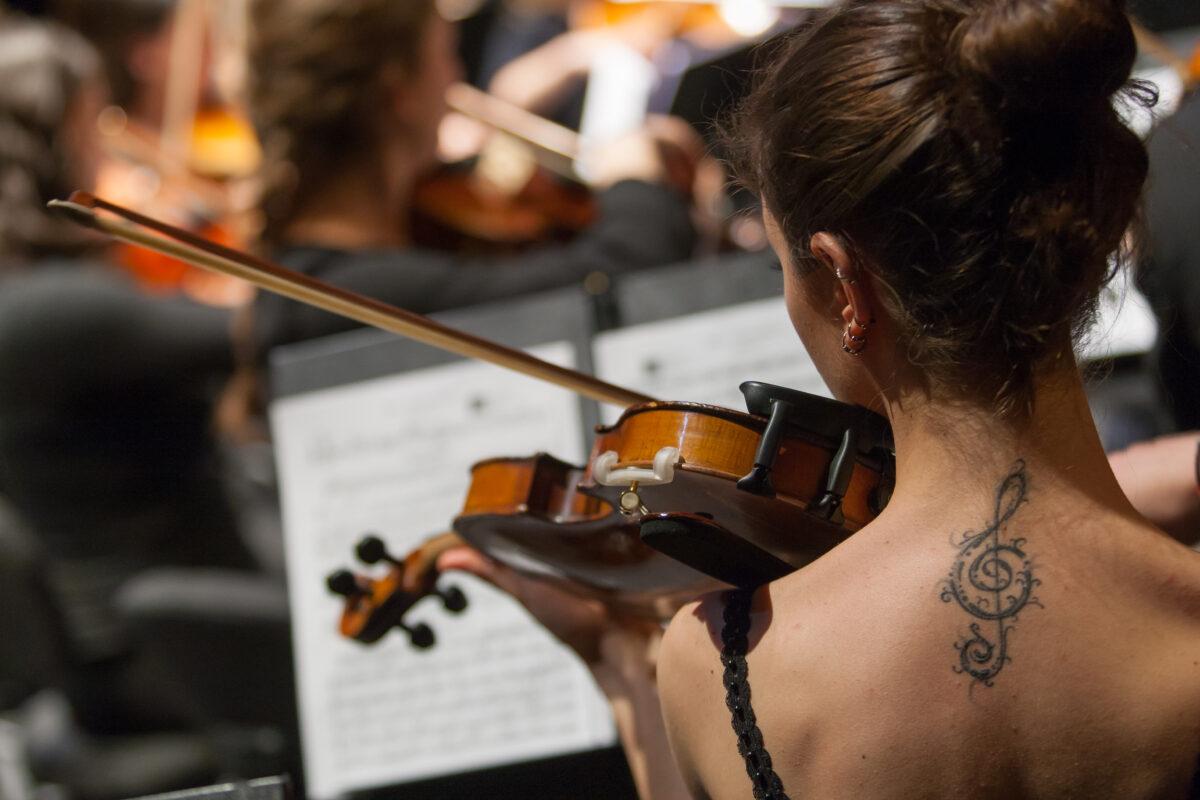 en la imagen, tomada desde detrás, la nuca de una violinista que toca su partitura