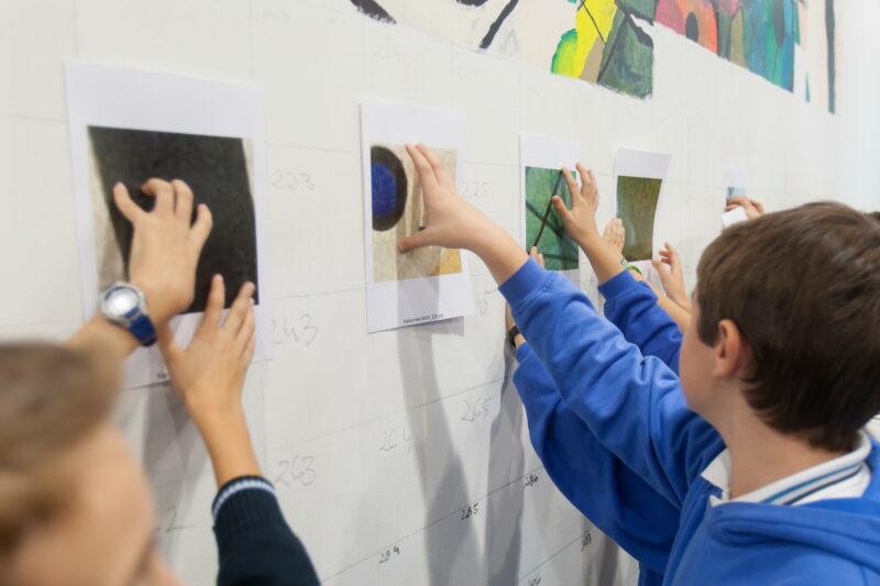 En la imagen los niños sostienen piezas que ellos mismos han confeccionado, y las colocan en el gran mural de pared que se realizará con sus aportaciones.