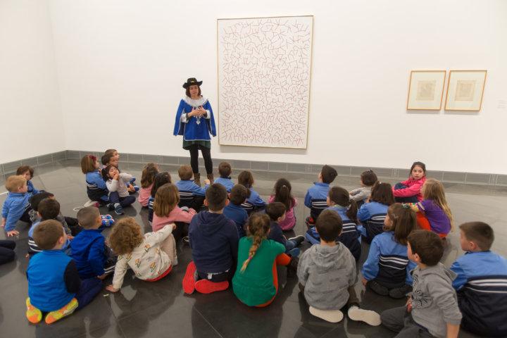 En la imagen una monitora vestida de mosquetero comparte con un grupo de niños sentados en el suelo ante el cuadro El Número y las Aguas de Palazuelo