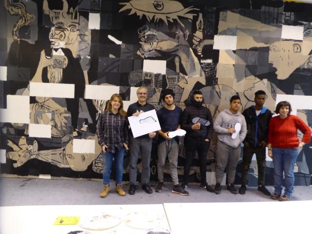 En la imagen un grupo de jóvenes posa satisfecho ante el mural colaborativo llevado a cabo en el proyecto Gernika