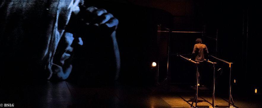 En la imagen una figura encapuchada se hace visera con la mano intentando atisbar un bailarín colgado en unas barras paralelas