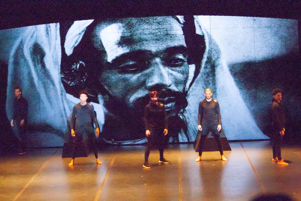 Sobre el escenario, varios bailarines danzan ante una imagen de una fotografía de un africano, forma parte de la coreografía Atlas 2 de Dani Pannullo