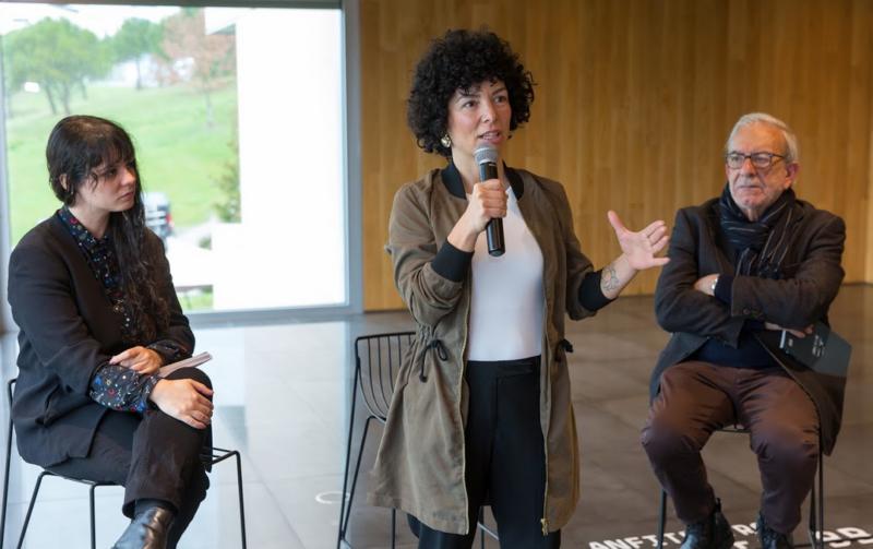En la fotografía, sentados en sillas altas de bar y ante un ventanal del Museo, Ibis Albizu, Itsaso Cano -que sujeta un micrófono y habla- y José Manuel Garrido en la presentación del Cuaderno de Creación de la coreógrafa.