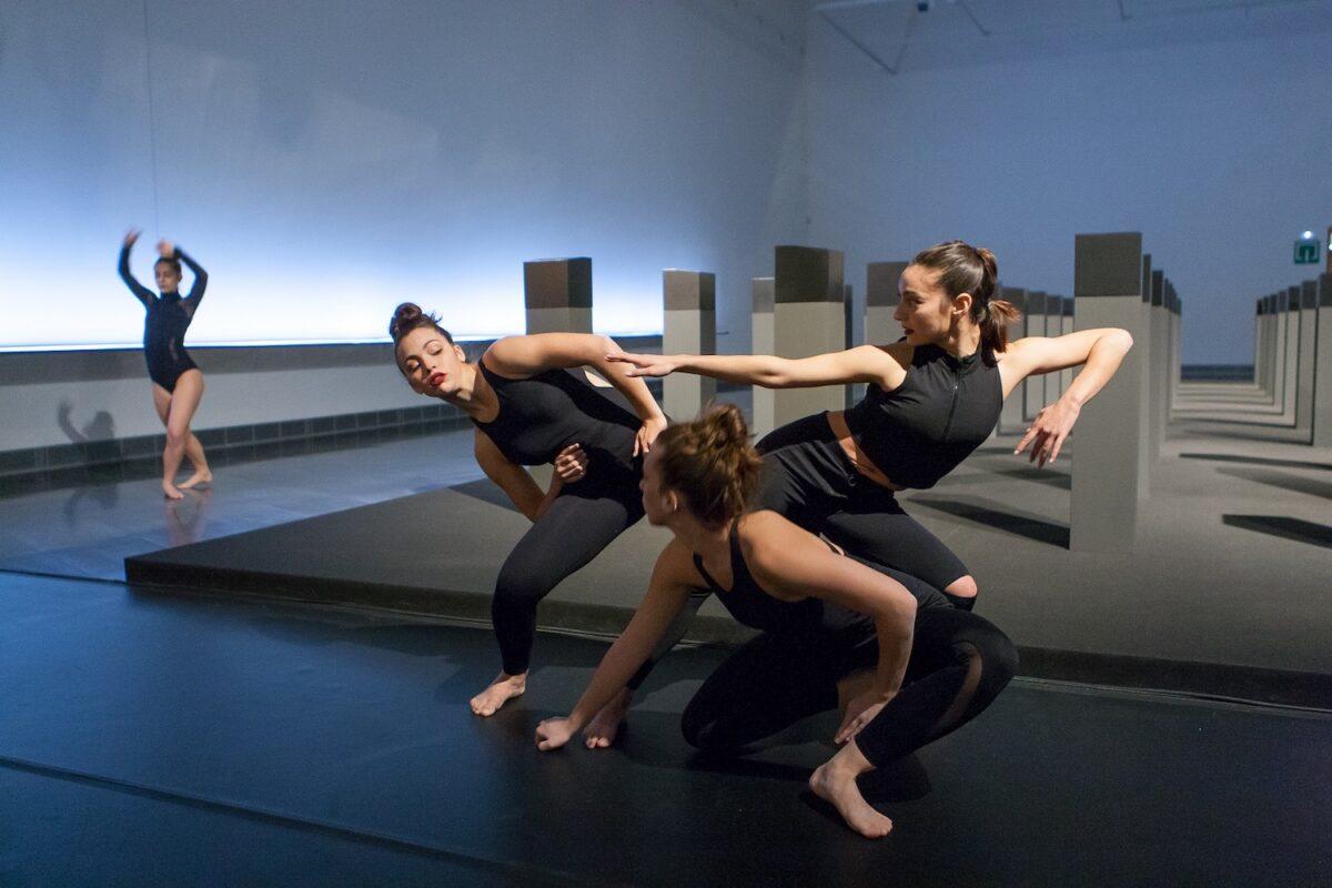 En la imagen varias bailarinas vestidas de negro evolucionan en una pieza que se danzó en las salas del Museo ante la obra Menhires de la exposición de Elena Assins.