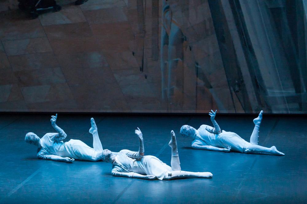 La producción Oskara de Kukai Dantza es un trabajo de reflexión sobre nuestras raices, la danza, la tradición, y las preguntas del ser humano, la comunicación. en la imagen una escena de esa coreografía, los bailarines bailan desde el suelo vestidos de blanco del pie a la cabeza que llevan cubierta por una tela de encaje como en la danza tradicional vasca.