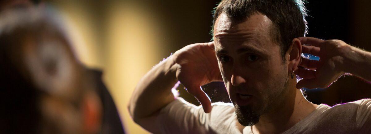En un primerísimo plano un bailarín con las manos en la nuca mira con preocupación hacia delante como si atisbase un futuro incierto .