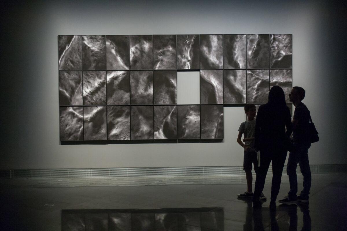 Tres personas observan un mosaico de Aitor Ortiz cuyo significado se presta a la interpretación.