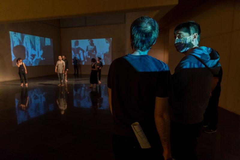 El bailarín Jon Maya habla con el realizador en la sala -1 del Museo. En las dos paredes del ángulo de la sala se proyectan las dos fotografías de Las Roncalesas de José Ortiz Echagüe realizadas en la gripe de 1919, delante ensayan los bailarines descalzos.