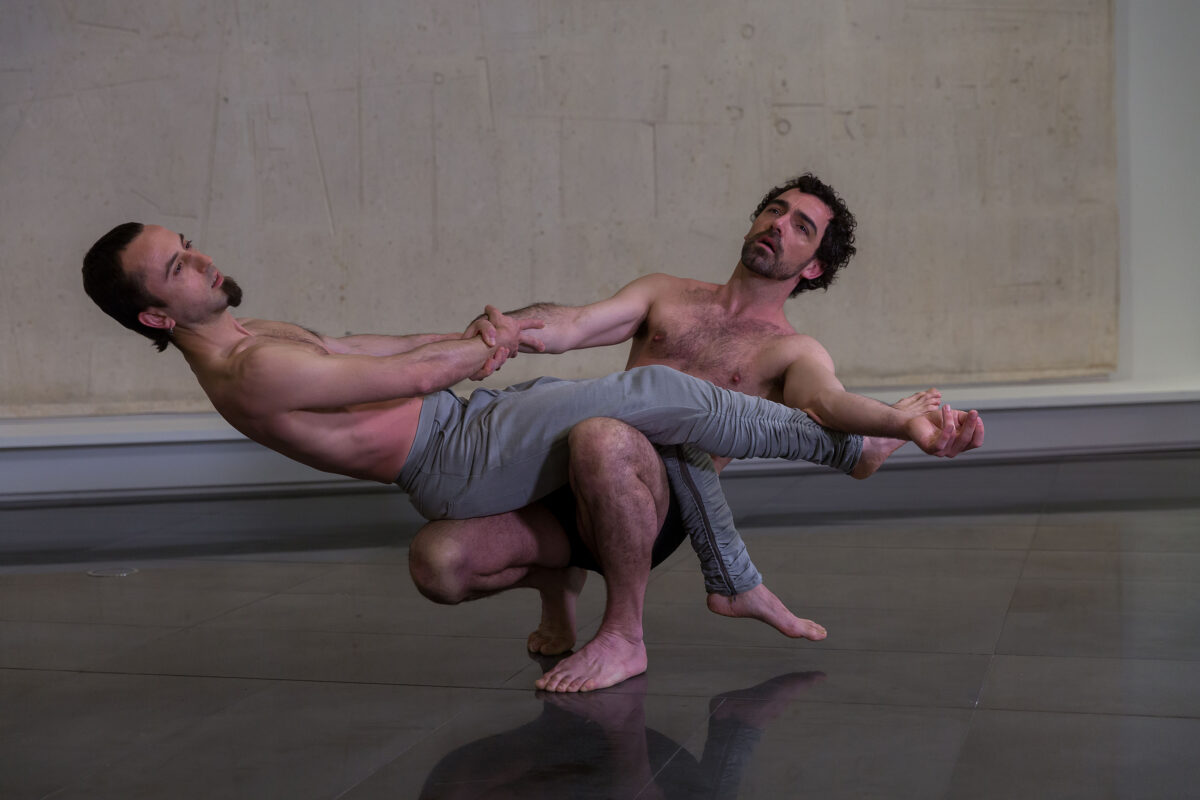 Dos bailarines en un momento de la danza ante la pieza Homenaje a Bach de Jorge Oteiza. El primer bailarín en cuclillas sujeta en equilibrio a un segundo bailarín en equilibrio. Ambos miran hacia arriba en actitud orante.