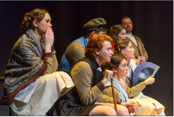Un grupo de estudiantes, vestidos de pequeñoburgueses del xix, aparecen sentados en diversas filas y miran expectantes a otros actores que no aparecen en la imagen